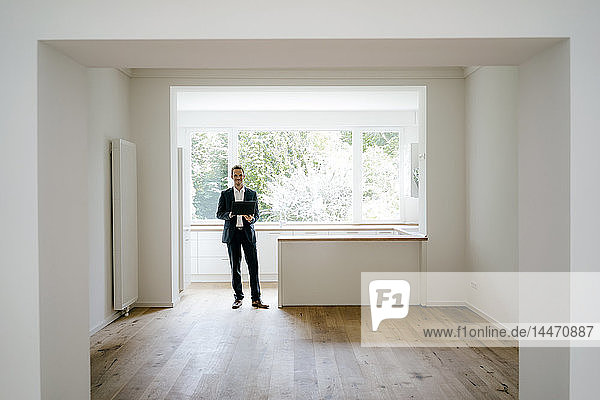 Estate agent waiting in newly refurbished home  holding laptop