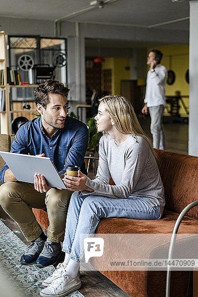 Geschäftsfrau und Geschäftsmann benutzen Tablett auf Sofa im Loft-Büro