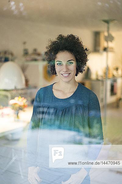 Porträt einer lächelnden Frau  die zu Hause hinter dem Fenster steht