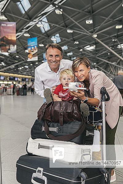 Porträt einer glücklichen Familie mit Gepäckwagen auf dem Flughafen