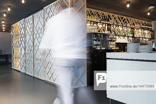 Ein verschwommener Mann geht an einem modernen Büro-Lounge-Bereich und einer Bar vorbei