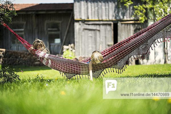 Zwei Kinder entspannen sich in der Hängematte im Garten eines Bauernhofs