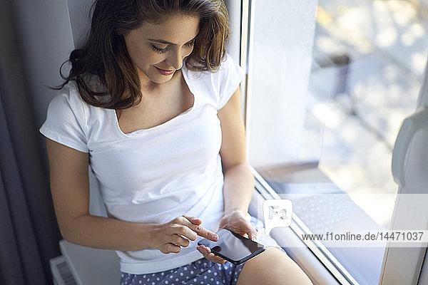 Junge Frau sitzt auf dem Fensterbrett und benutzt ein Smartphone
