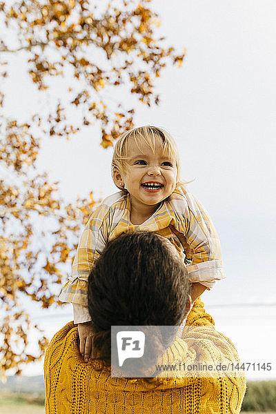 Vater hält seine Tochter an einem Morgen im Herbst im Park