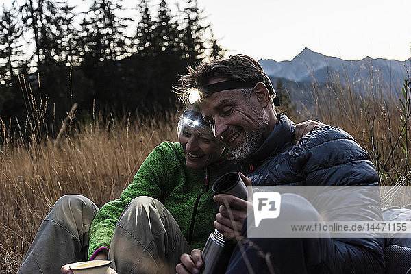 Wanderndes Ehepaar macht abends eine Pause  trägt Stirnlampen  trinkt Tee