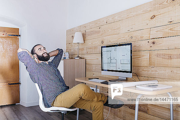 Smiling young man sitting at desk with floor plan on the computer