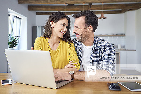 Couple sitting at dining table  using laptop  smiling