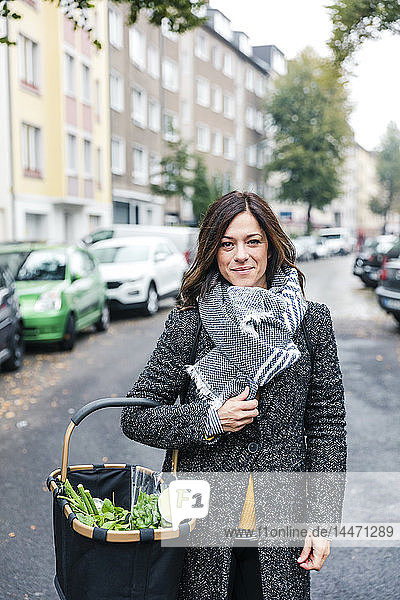 Mature woman standing in the street  carrying shopping basket with fresh vegetables