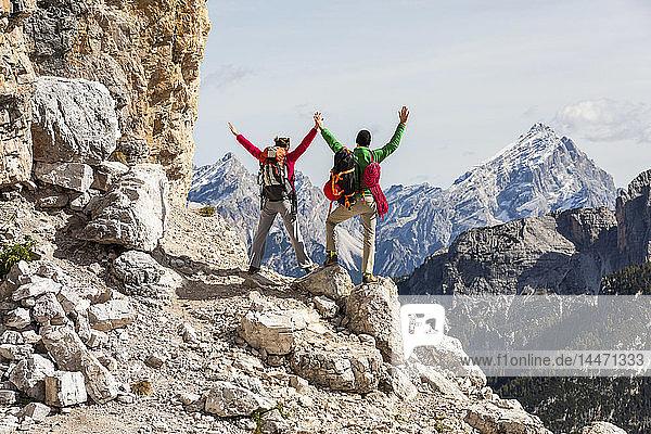 Italien  Cortina d'Ampezzo  Ehepaar mit Seil und Kletterausrüstung  Blick mit erhobenen Armen
