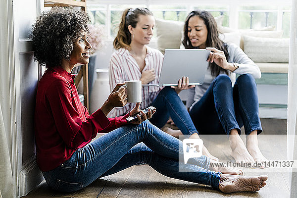 Three women with cell phone  coffee cup and laptop sitting on the floor at home