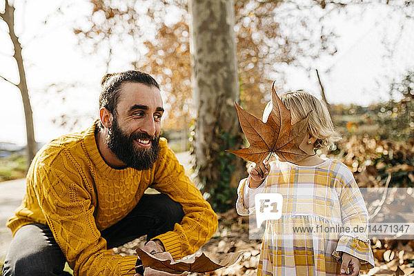 Vater und Tochter genießen im Herbst einen Vormittag im Park und spielen mit Herbstblättern