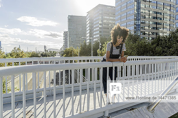 Junge Frau steht auf einer Brücke  benutzt ein Smartphone und hat Kopfhörer um den Hals