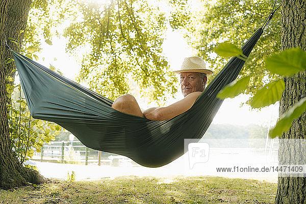 Älterer Mann mit Strohhut entspannt sich in Hängematte am Seeufer