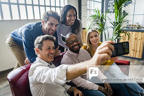 Fröhliches Geschäftsteam beim Selfie im Loft-Büro