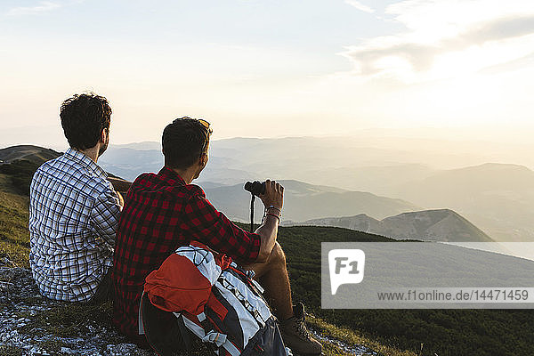 Italy  Monte Nerone  two hikers on top of a mountain enjoying the view at sunset