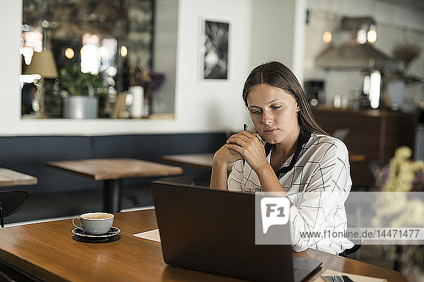 Young businesswoman in a cafe working with laptop on wooden table