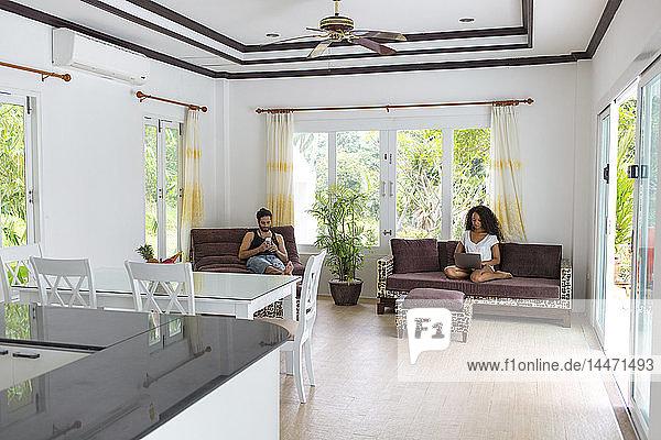 Thailand  Ehepaar sitzt in geräumigem Wohnzimmer am Ferienort und benutzt elektronische Geräte