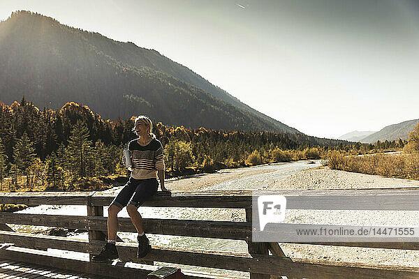 Österreich  Alpen  glückliche Frau auf einer Wanderung mit Pause auf einer Brücke
