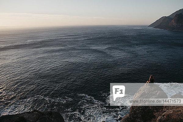 Südafrika  Westkap  Frau sitzt auf einem Felsen und schaut auf die Aussicht  gesehen vom Chapman's Peak Drive