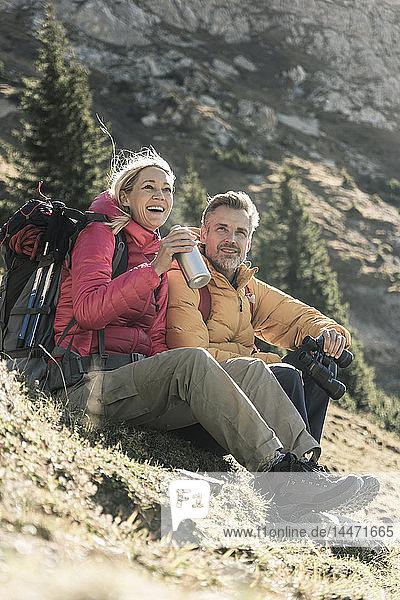 Österreich  Tirol  glückliches Paar macht Pause während einer Wanderung in den Bergen