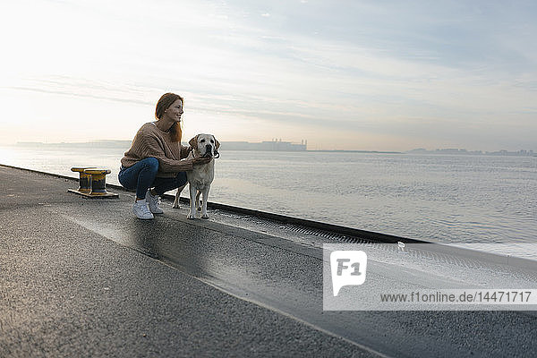 Germany  Hamburg  woman with dog on pier at the Elbe shore