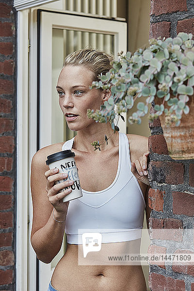 Sporty young woman with takeaway drink at house entrance