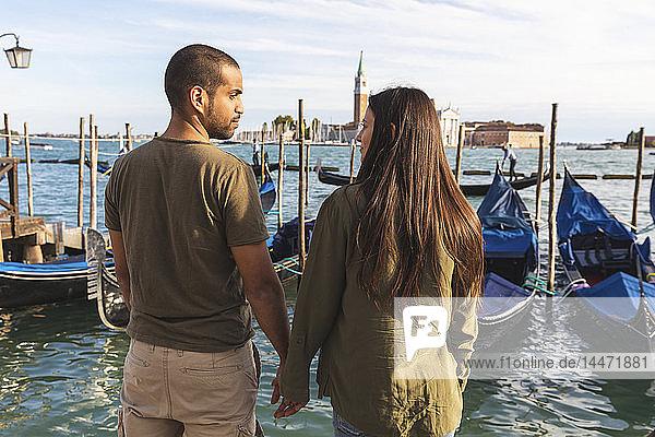 Italien  Venedig  liebevolles junges Paar mit Gondelbooten im Hintergrund