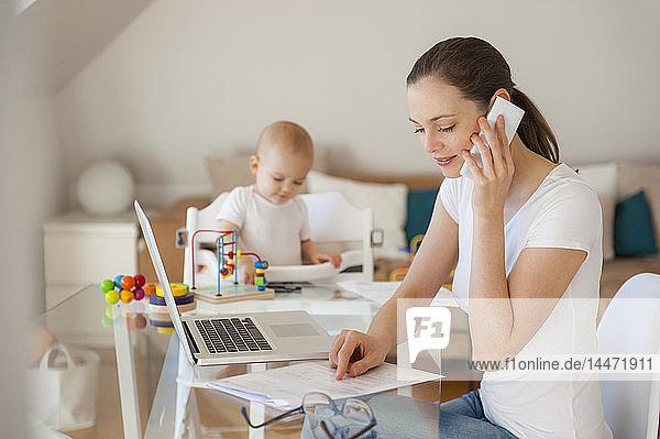 Mutter arbeitet und kleine Tochter spielt zu Hause am Tisch