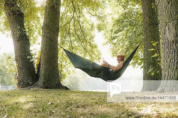 Älterer Mann mit Strohhut entspannt sich in Hängematte am Seeufer und liest Buch
