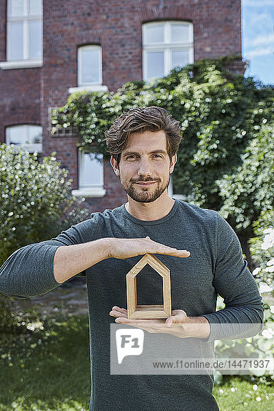 Portrait of confident man in front of his home holding house model