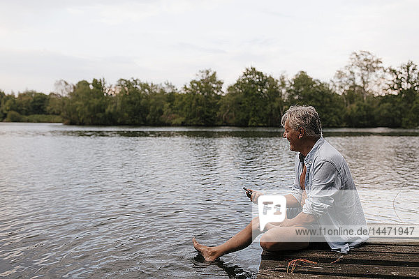 Happy senior man sitting on jetty at a lake with cell phone