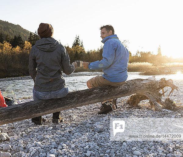 Ein erwachsenes Paar zeltet am Flussufer im Abendlicht