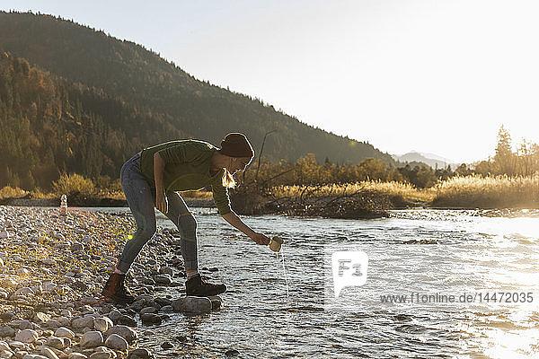 Reife Frau am Flussufer mit Becher