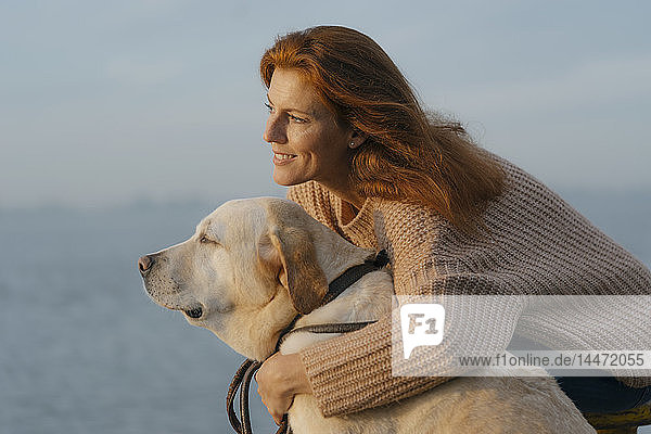 Deutschland  Hamburg  glückliche Frau kuschelt mit Hund am Elbufer