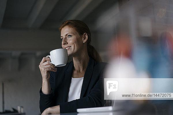 Lächelnde Geschäftsfrau mit Tasse Kaffee am Schreibtisch im Büro sitzend