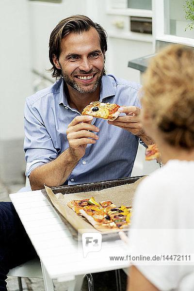 Glückliches Paar sitzt im Garten  isst Pizza  trinkt Wein