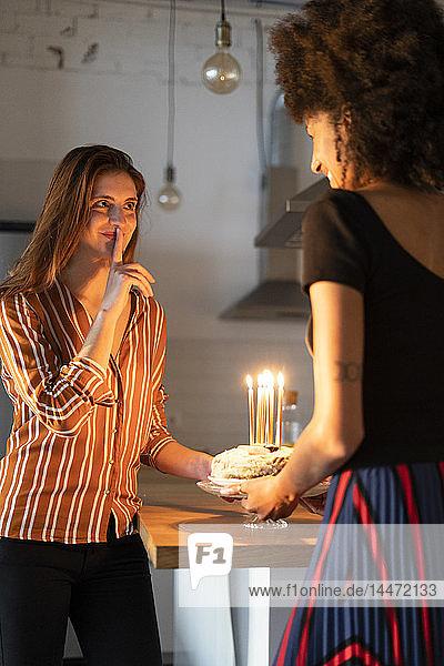 Freunde bereiten einen Geburtstagskuchen mit brennenden Kerzen als Überraschung zu