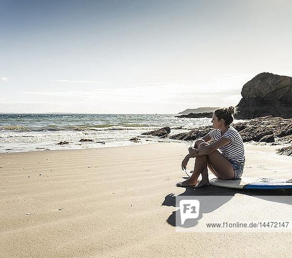 Junge Frau sitzt auf ihrem Surfbrett am Strand und schaut auf das Meer