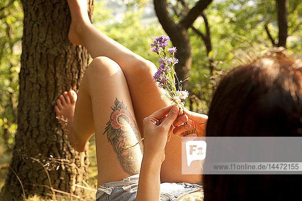 Junge Frau in waldgebundenem Blumenstrauss
