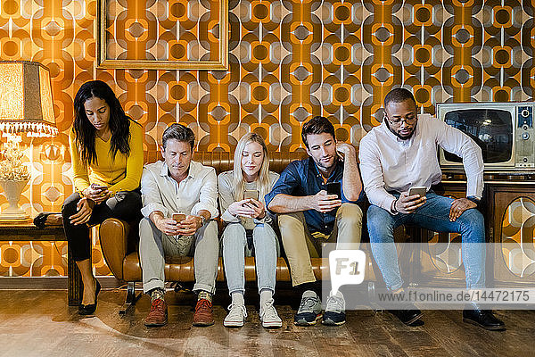 Group of people sitting on couch in vintage living room using cell phones