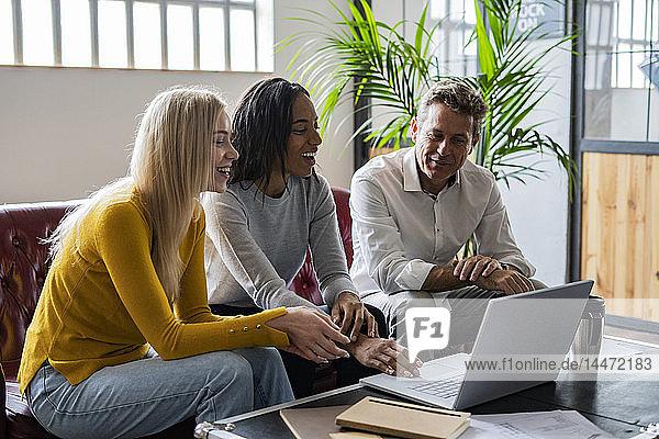 Glückliches Geschäftsteam mit Laptop auf der Couch sitzend im Loft-Büro