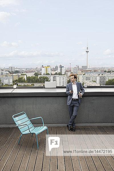 Deutschland  Berlin  Geschäftsmann entspannt sich auf der Dachterrasse bei einem Drink