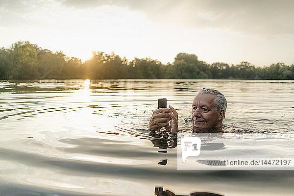 Älterer Mann schwimmt bei Sonnenuntergang mit seinem Handy in einem See