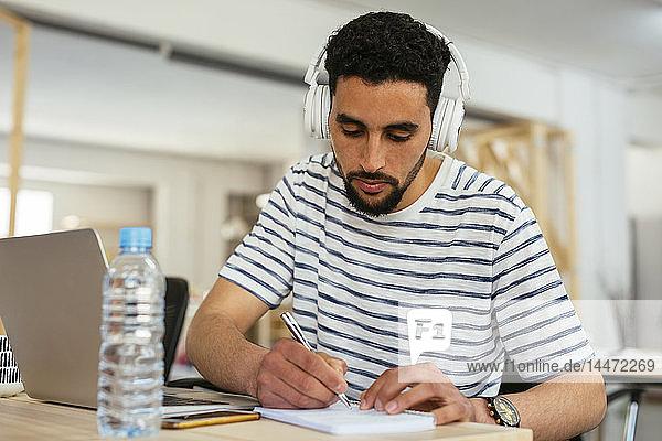 Junger Mann mit Kopfhörern macht Notizen am Schreibtisch im Büro