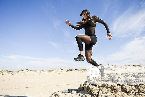 Sportliche Frau springt am Strand von Steinmauer