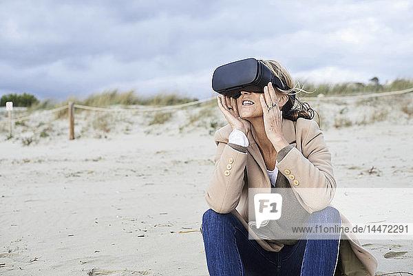 Spanien  Menorca  ältere Frau mit VR-Brille am Strand im Winter