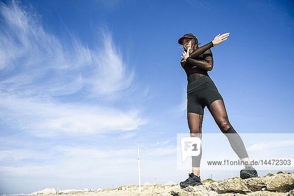 Sportliche Frau steht auf Steinmauer und macht Streckübungen
