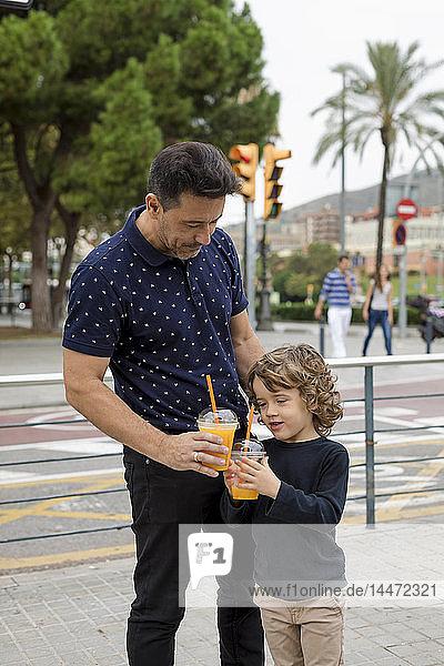 Vater und Sohn mit Erfrischungsgetränken in der Stadt
