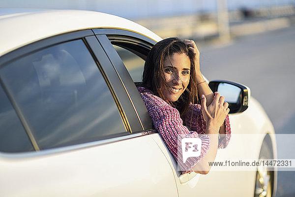 Porträt einer lächelnden Frau  die aus dem Autofenster schaut