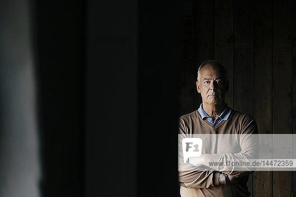 Porträt eines seriösen älteren Geschäftsmannes vor einer Holzwand